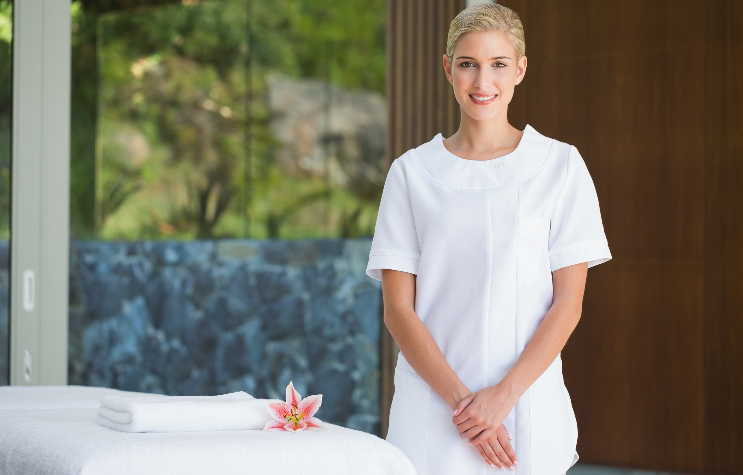 Young adult woman with tied back blonde hair stands next to a spa bed, wearing a white spa uniform, holding her hands in front of her as she wears a fake smile, covering up her therapist burnout.