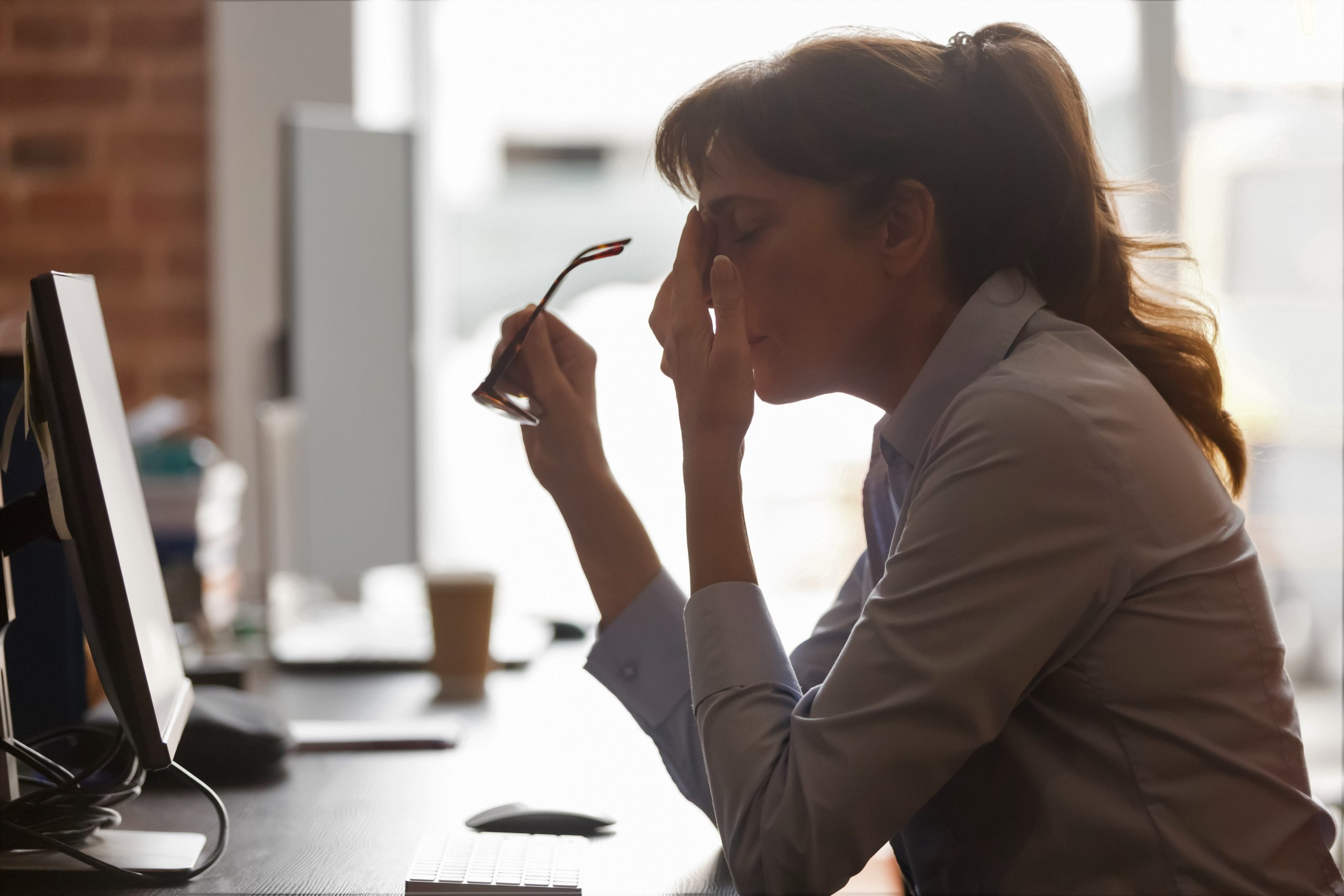 Young adult woman wearing a business suit taking off her glasses in despair as she displays staff negativity after returning back to work